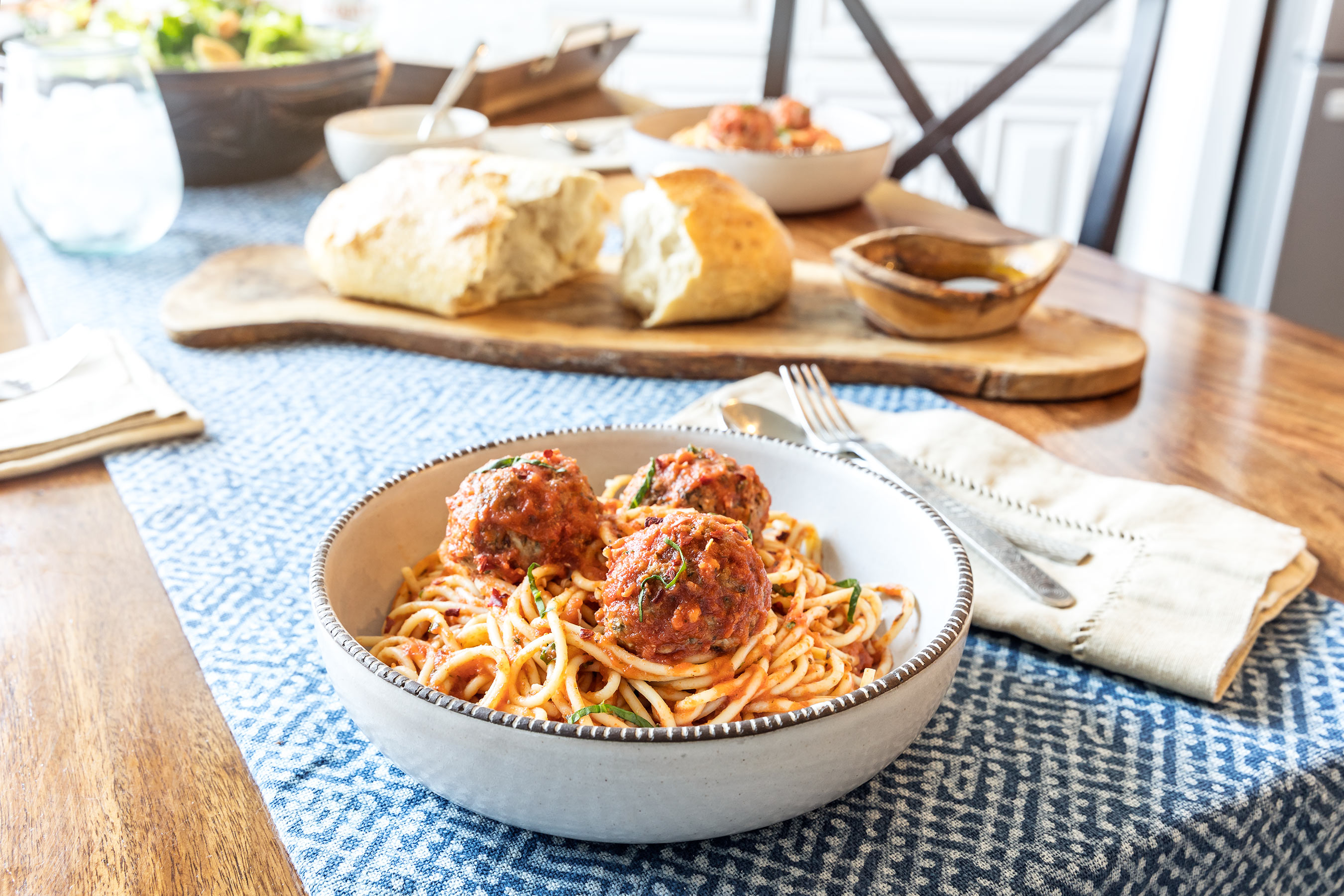 Spaghetti and meatballs on a table with bread and salad in the back