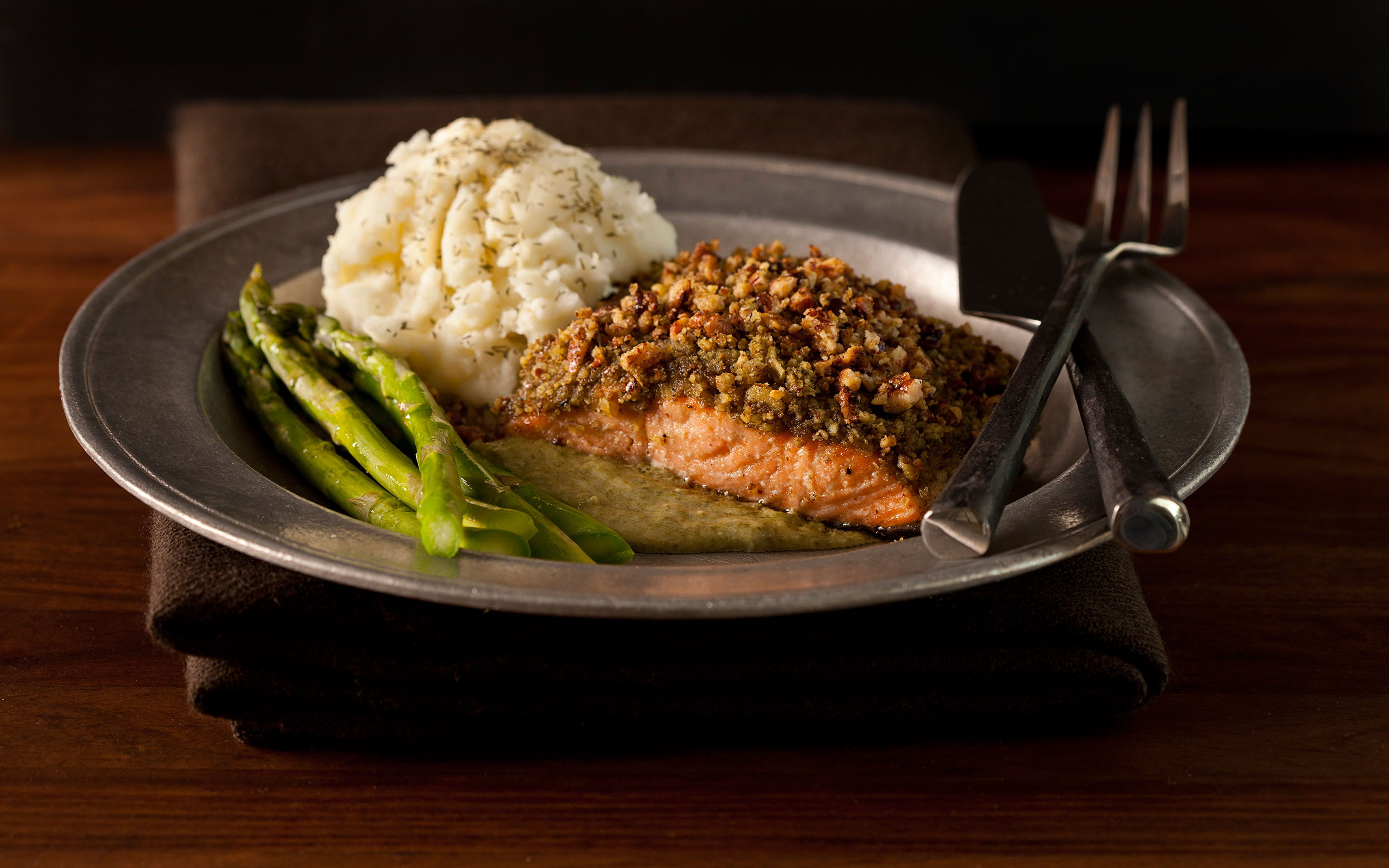 Pistachio crusted salmon on metal plate w/ mashed potatoes & asparagus