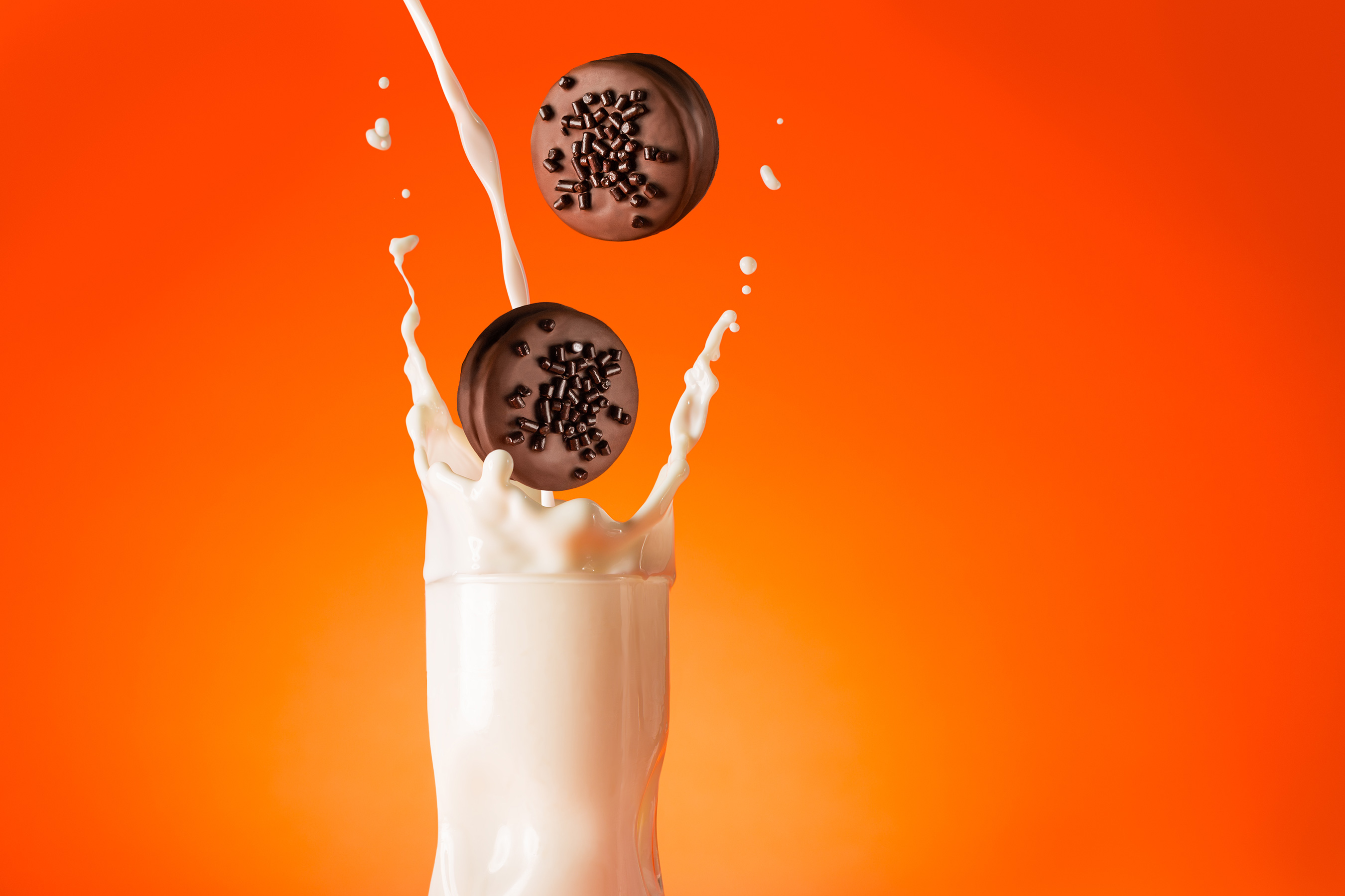 Marinela Gansito cookies dropping into splashing milk w orange background