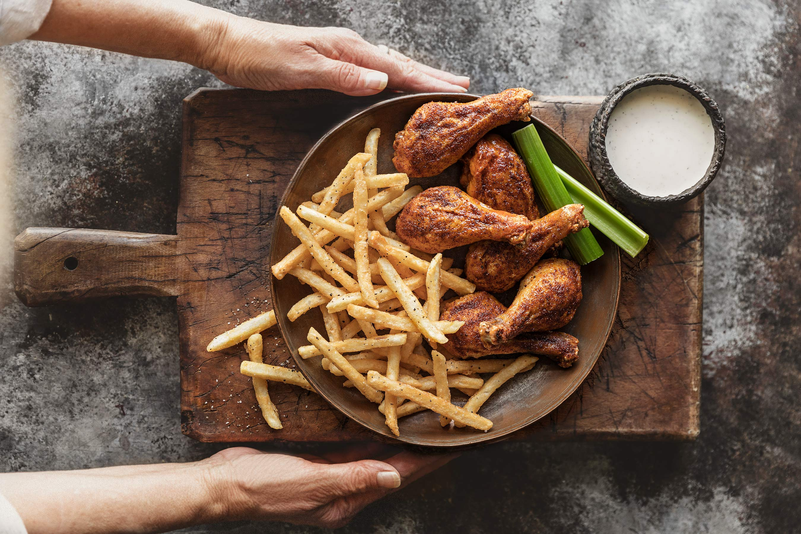 Drumsticks and Fries with celery and ranch.  Hands serving it on a wood board