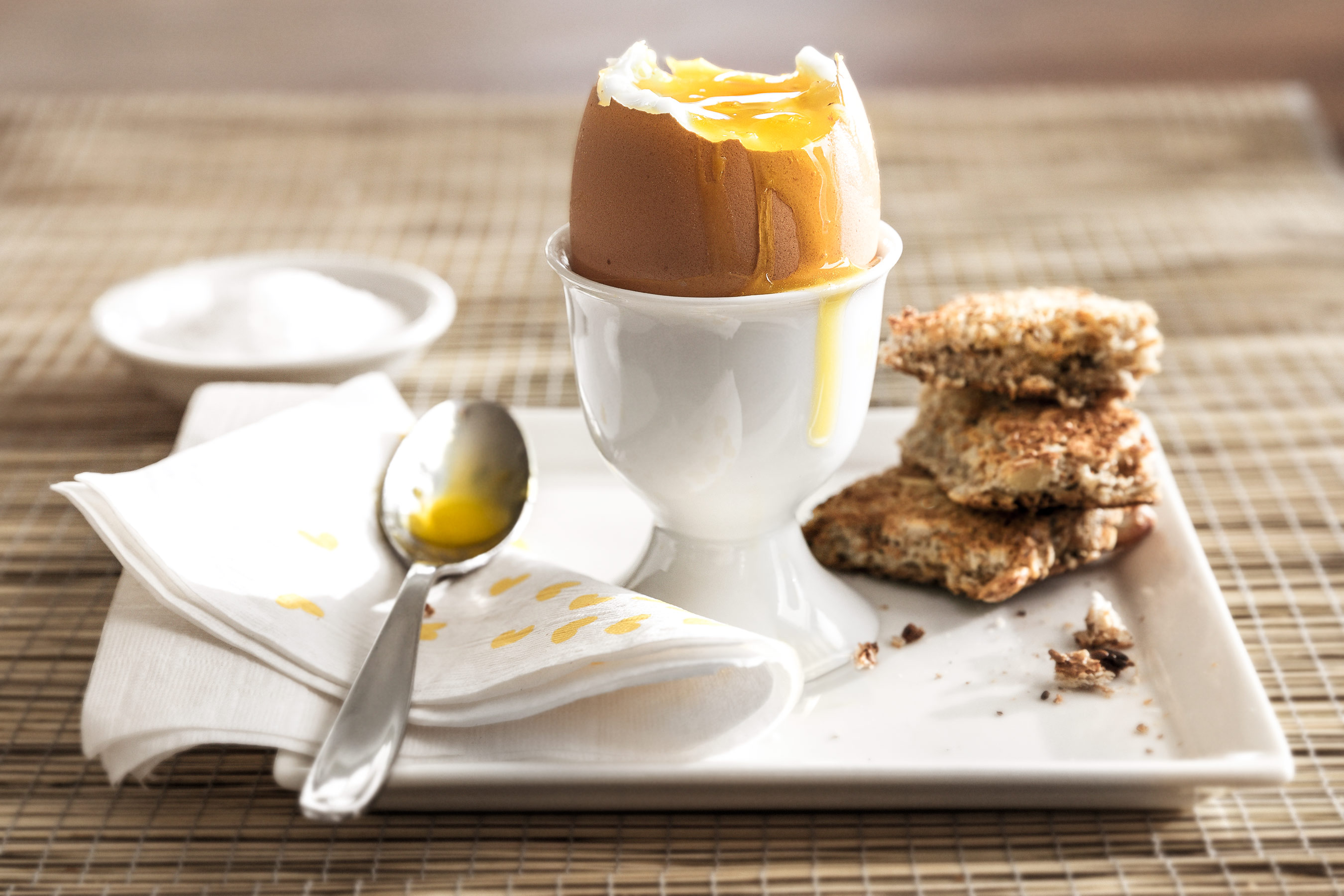 Soft boiled egg in an egg cup with toast bites and salt on side