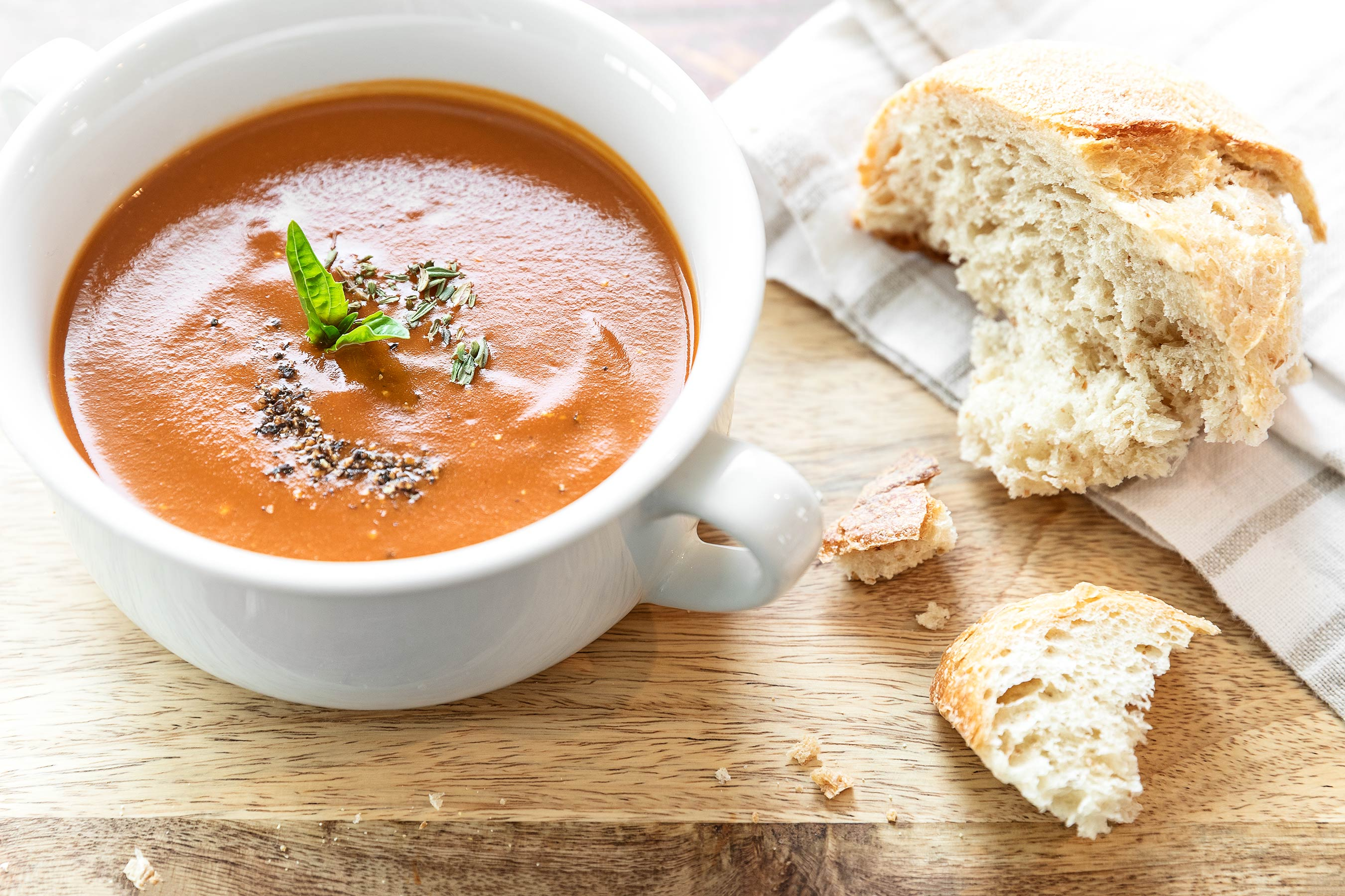 tomato basil soup shot overhead with black pepper and rustic bread