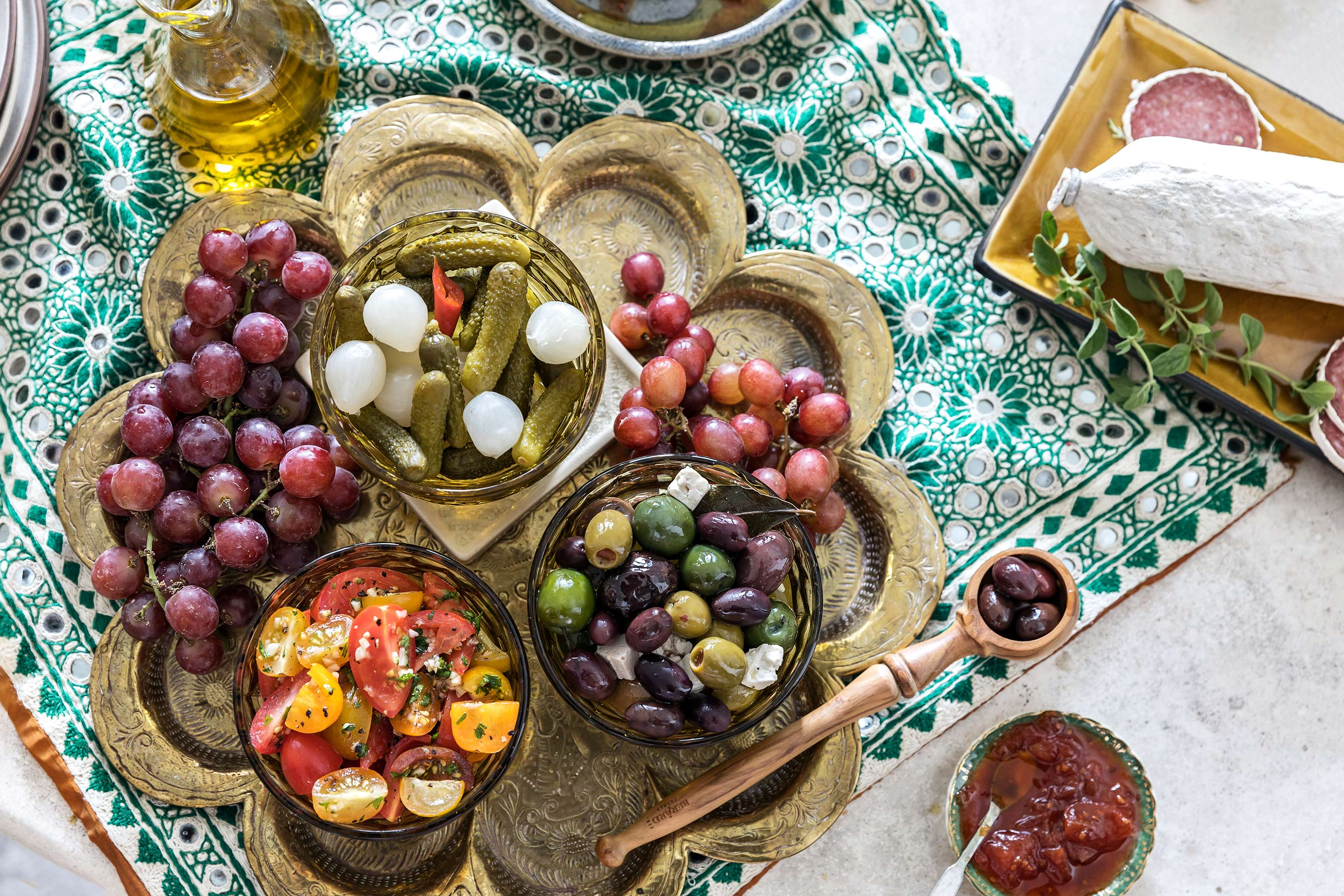 Mediterranean platter with olives, tomatoes, gherkins and grapes.
