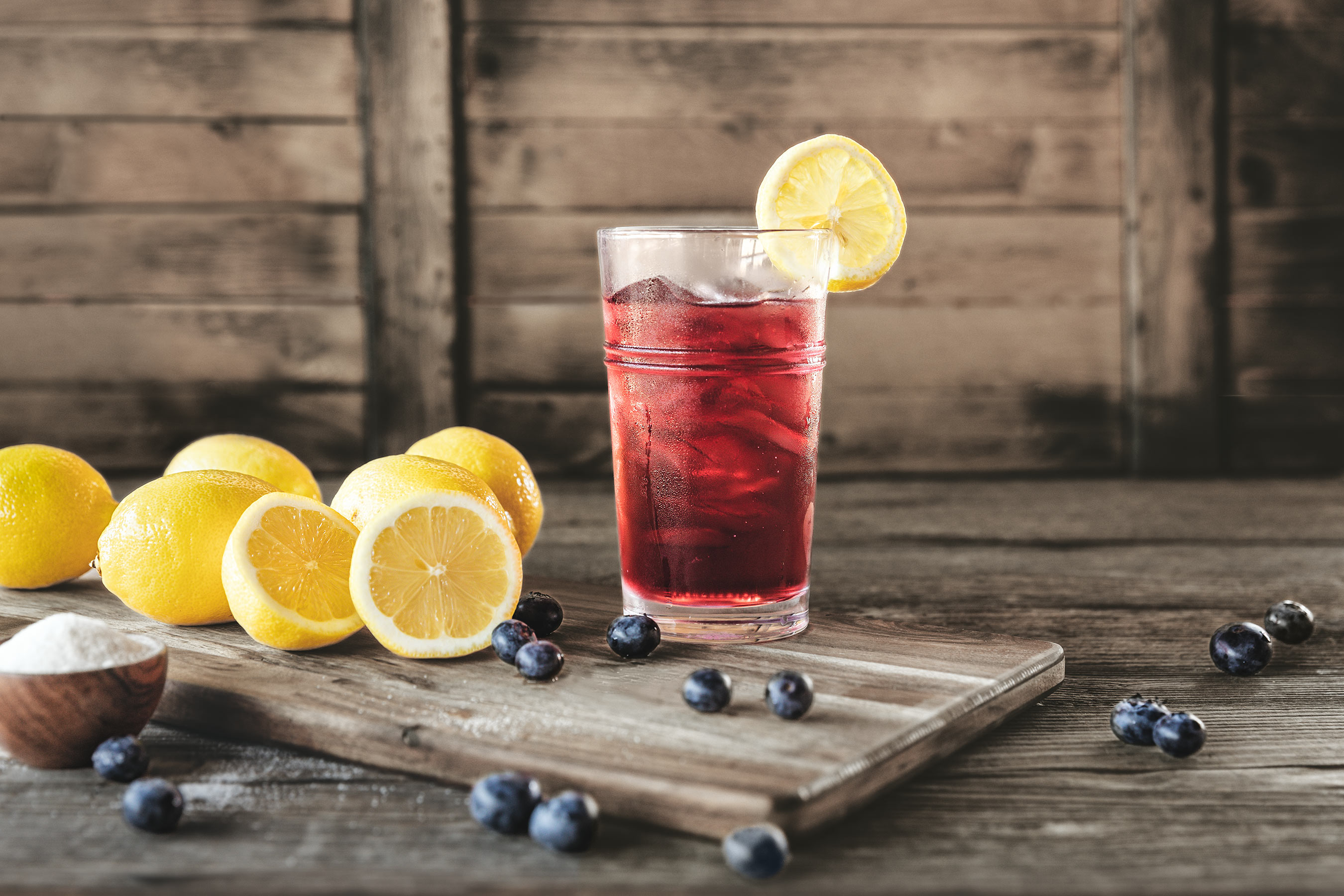 Blueberry Lemonade in a glass with ice in a rustic barn environment