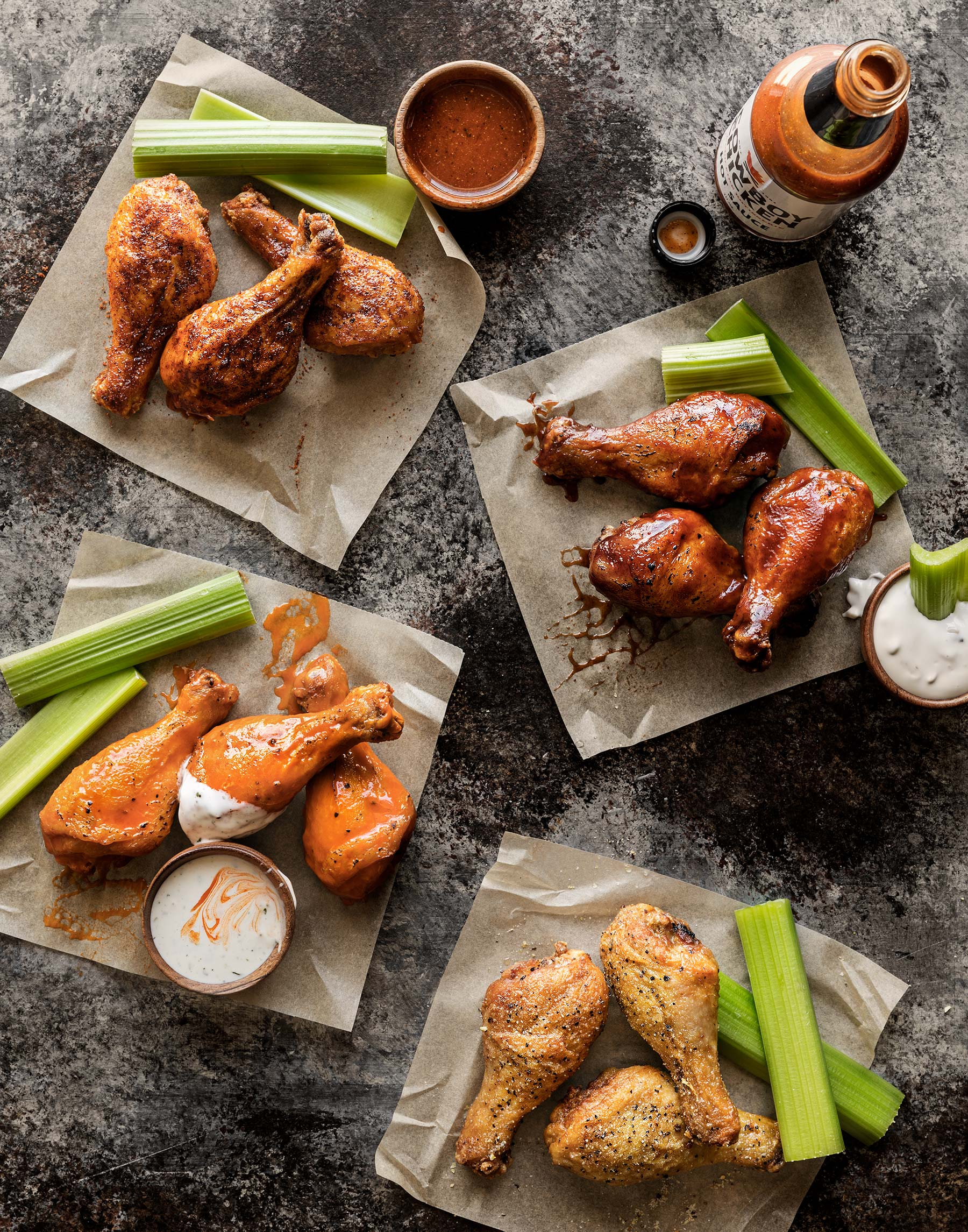 Group of drumsticks with hot sauces shot overhead for Cowboy Chicken