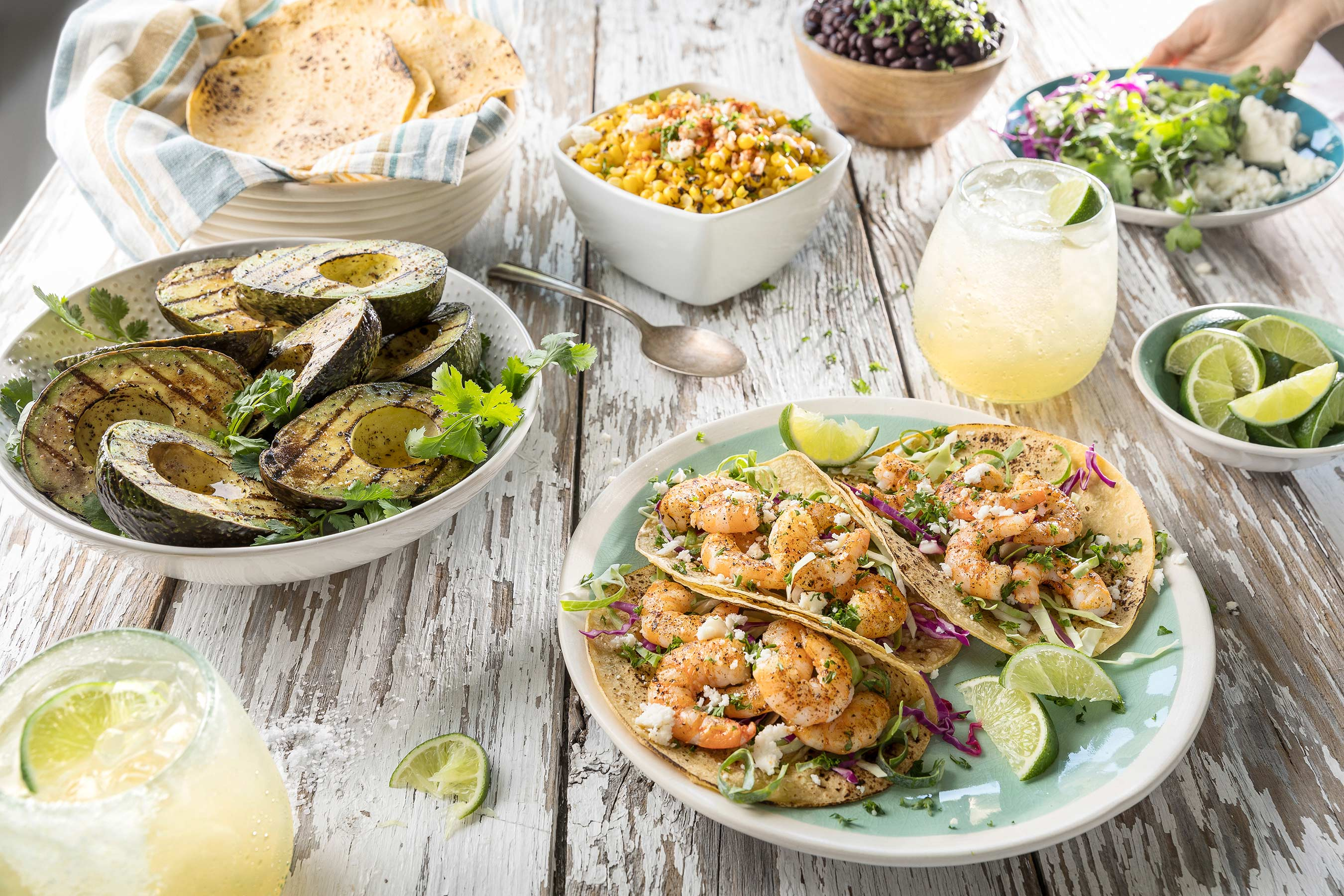 Shrimp Tacos with margarita's, elotes, black beans, avocado and limes