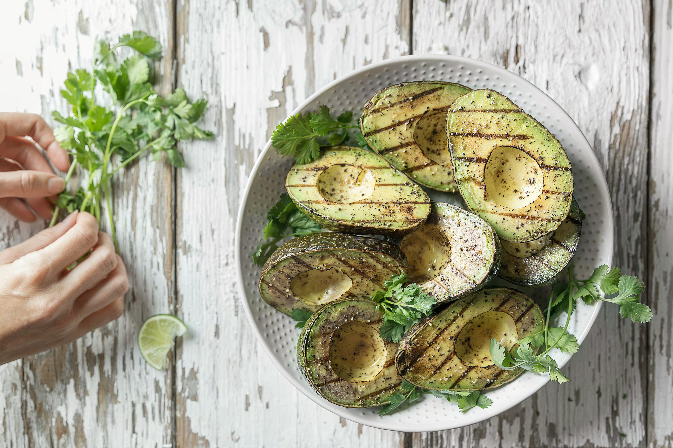 Halved Grilled Avocados with hands placing cilantro and lime