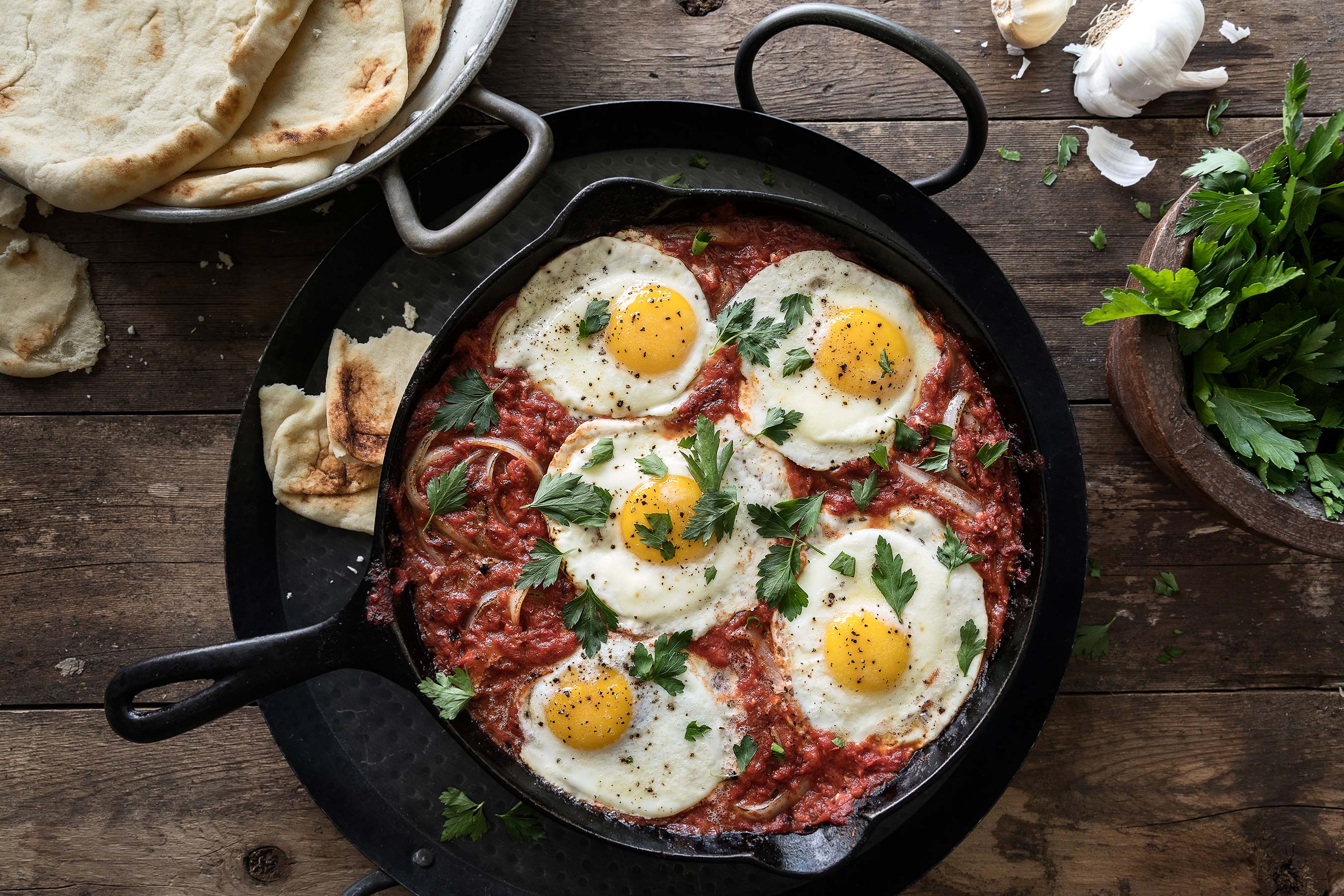Shakshuka in cast iron pan with pita bread, parsley and garlic