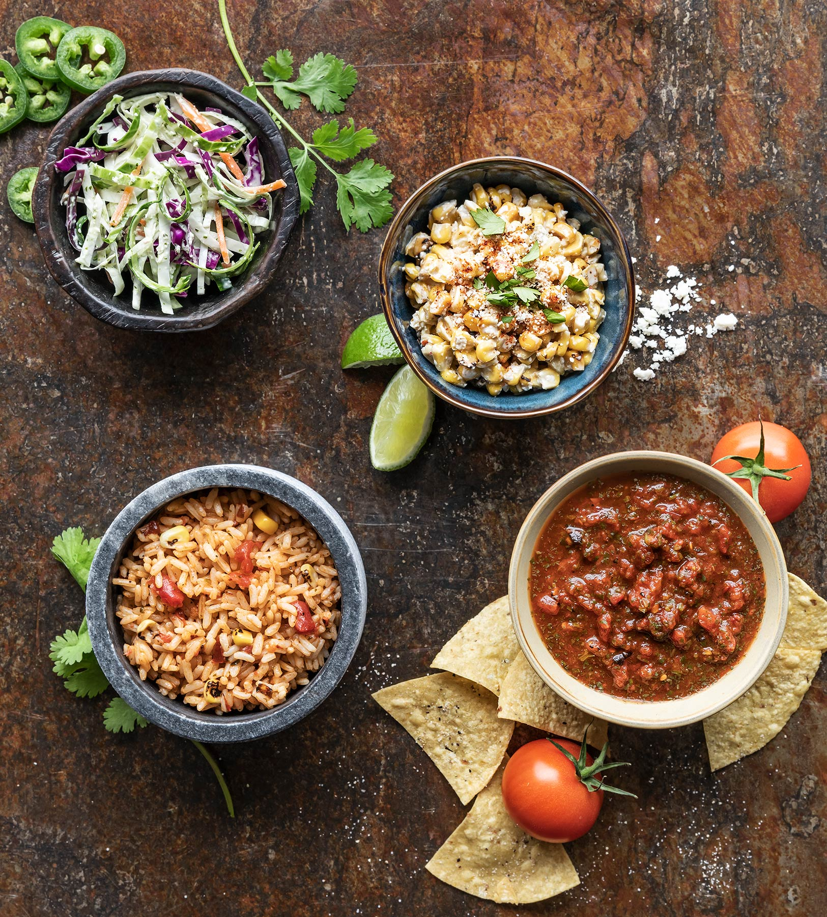 Side bowls of slaw, Elotes, red rice, chips & salsa on rustic metal