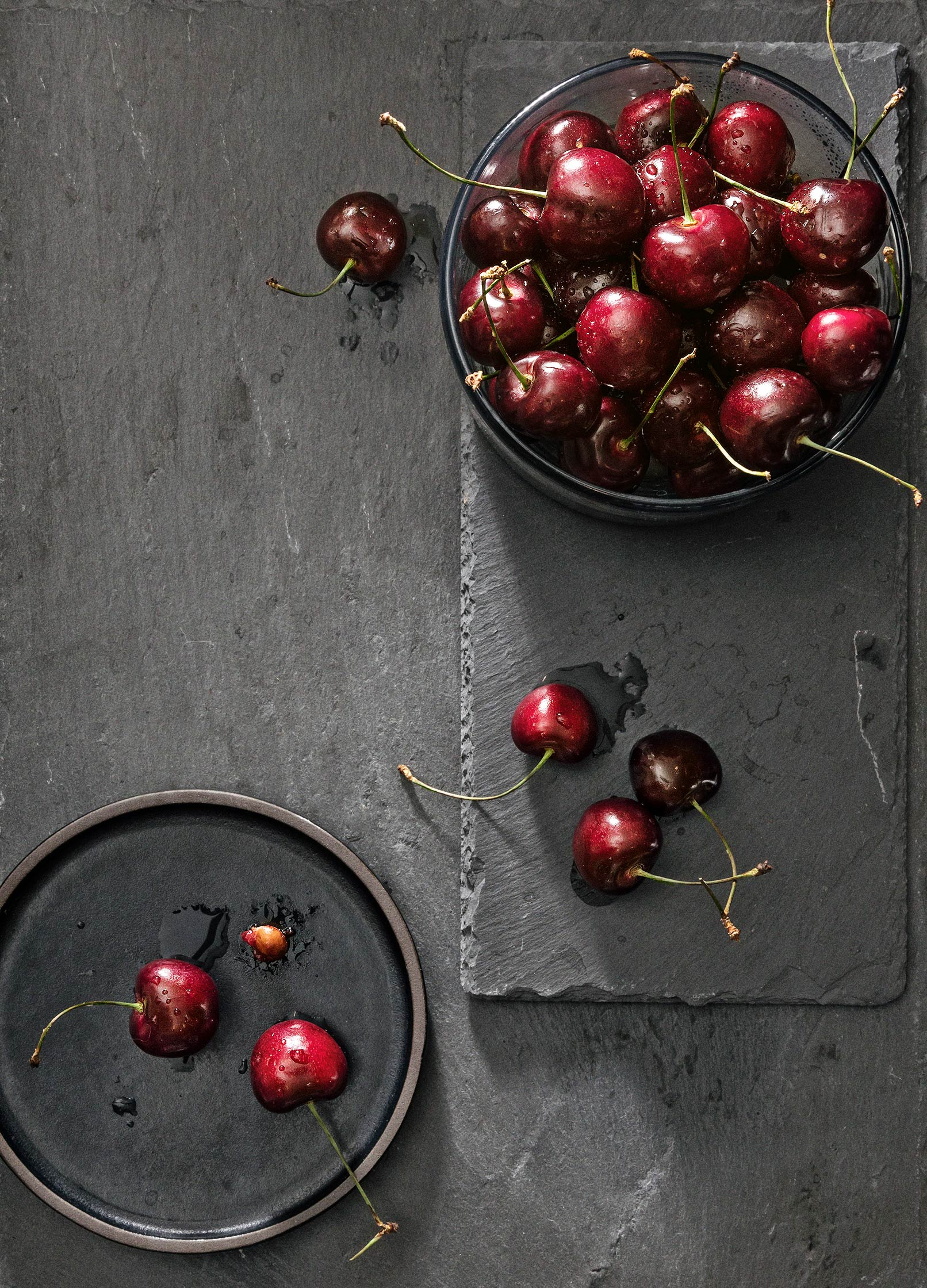 Overhead of cherry bowl with 2 cherries on a side plate on slate surface
