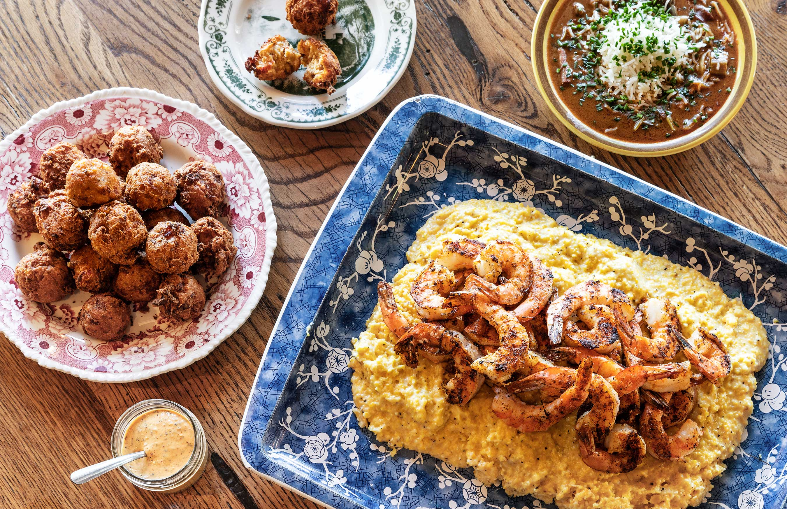 Blue platter of shrimp on rice with hush puppies + beans on a wood surface